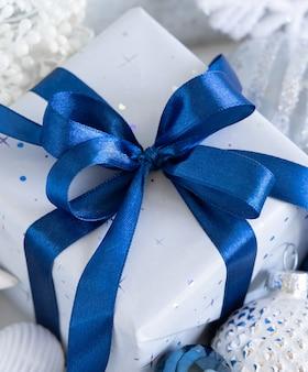 Обернутый подарок с голубым бантом и белыми, синими и серебряными рождественскими украшениями вокруг крупного плана. зимняя композиция