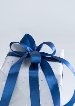 コピースペースと灰色の背景のクローズアップに青い弓で包まれたプレゼント。冬の作曲
