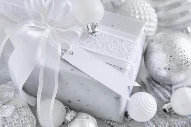 Обернутый подарок с белым бантом и бумажной подарочной биркой на белом столе с белыми и серебряными рождественскими украшениями крупным планом. зимняя композиция с пустой этикеткой, макет, копией пространства