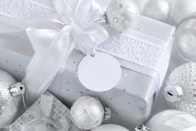 Обернутый подарок с белым бантом и круглой бумажной подарочной биркой на белом столе с белыми и серебряными рождественскими украшениями крупным планом. зимняя композиция с пустой этикеткой, макет, копией пространства