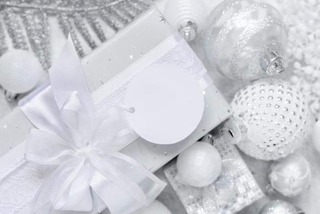 Обернутый подарок с белым бантом и круглой бумажной подарочной биркой на белом столе с белыми и серебряными рождественскими украшениями. зимняя композиция с пустой этикеткой, макет, копией пространства