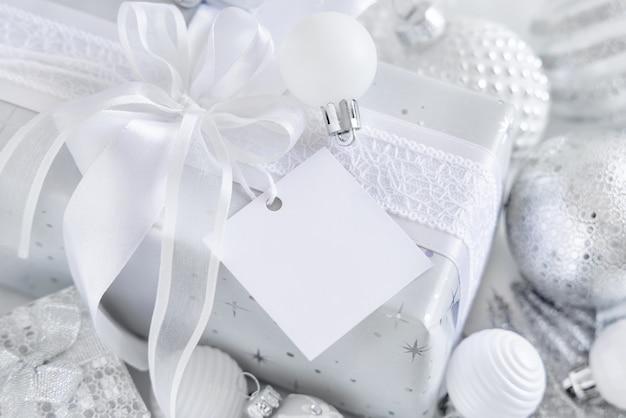 Обернутый подарок с белым бантом и квадратной бумажной подарочной биркой на белом столе с белыми и серебряными рождественскими украшениями крупным планом. зимняя композиция с пустой этикеткой, макет, копией пространства