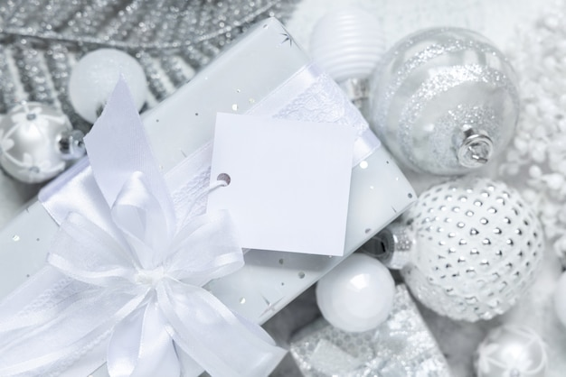 Обернутый подарок с белым бантом и квадратной бумажной подарочной биркой на белом столе с белыми и серебряными рождественскими украшениями, вид сверху. зимняя композиция с пустой этикеткой, макет, копией пространства