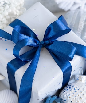 Wrapped present with a blue bow and white, blue and silver christmas decorations around closeup. winter composition