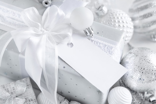 Wrapped present with a white bow and paper gift tag on a white table with white and silver christmas decorations close up. winter composition with blank label card, mockup, copy space