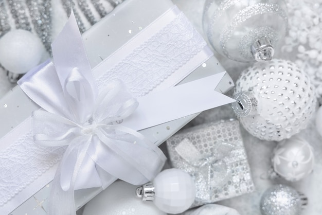 Wrapped present with a white bow and paper gift tag on a white table with white and silver christmas decorations top view. winter composition with blank label card, mockup, copy space