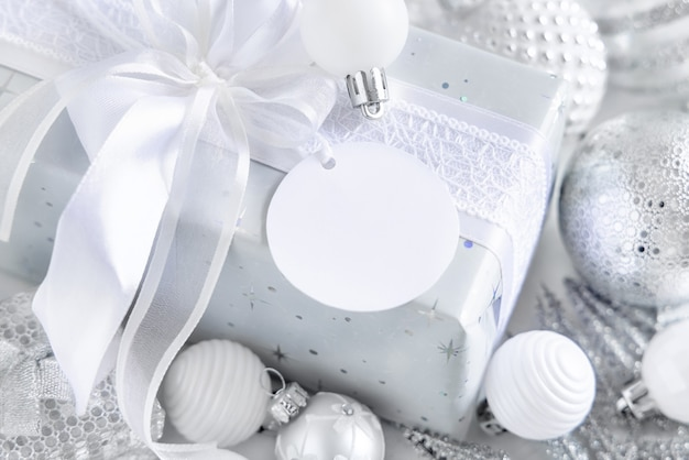 Wrapped present with a white bow and round paper gift tag on a white table with white and silver christmas decorations close up. winter composition with blank label card, mockup, copy space