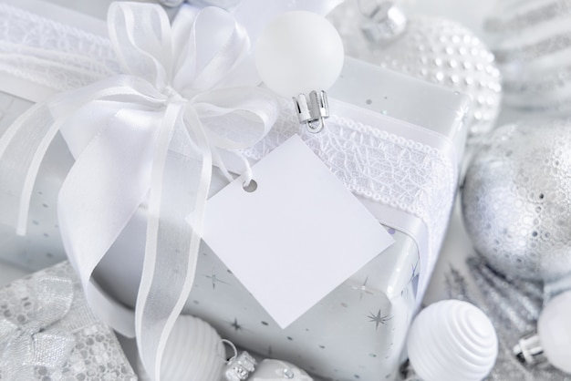 Wrapped present with a white bow and square paper gift tag on a white table with white and silver christmas decorations close up. winter composition with blank label card, mockup, copy space