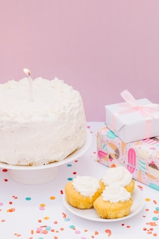 Wrapped presents; cupcake and cake with candle on birthday against pink backdrop