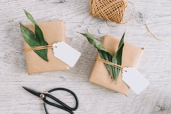 Wrapped presents with tag and leaves; spool and scissor on wooden textured background