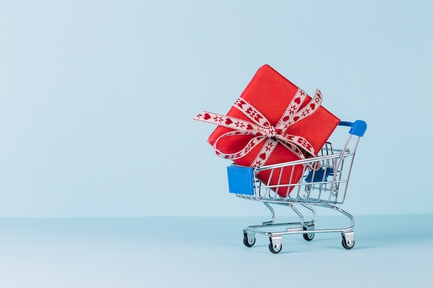 Wrapped red gift box in shopping cart on blue background