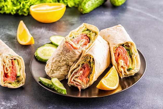 Обернутый бутерброд с лососем, листьями салата, огурцом и сливочным сыром, выборочный фокус.