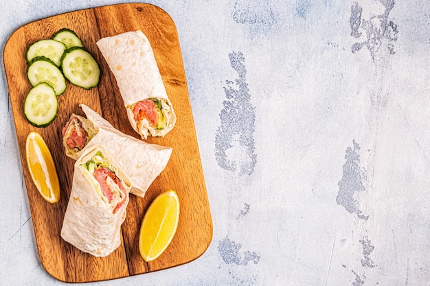 Обернутый бутерброд с лососем, листьями салата, огурцом и сливочным сыром, вид сверху.