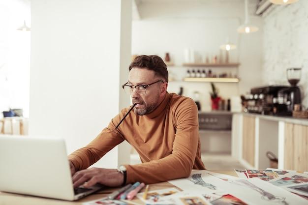 일에 싸여. 그의 입에 연필을 들고 노트북에서 빠르게 입력하는 열정적 인 잘 생긴 패션 디자이너.