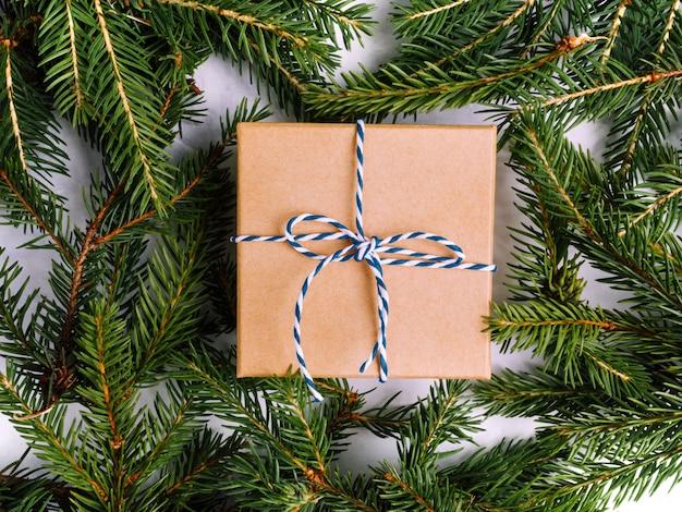 モミの木の枝と青いリボンで包まれたビンテージギフトボックス。クリスマスフラットが横たわっていた。