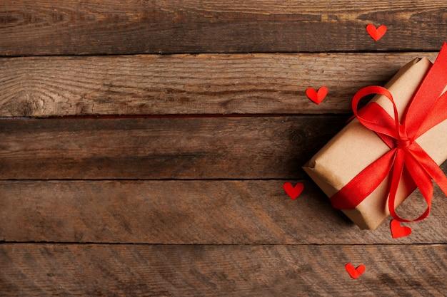 복사 공간, 발렌타인 데이 인사말 카드와 어두운 나무 테이블에 빨간 리본 활과 마음으로 포장 된 빈티지 선물 상자