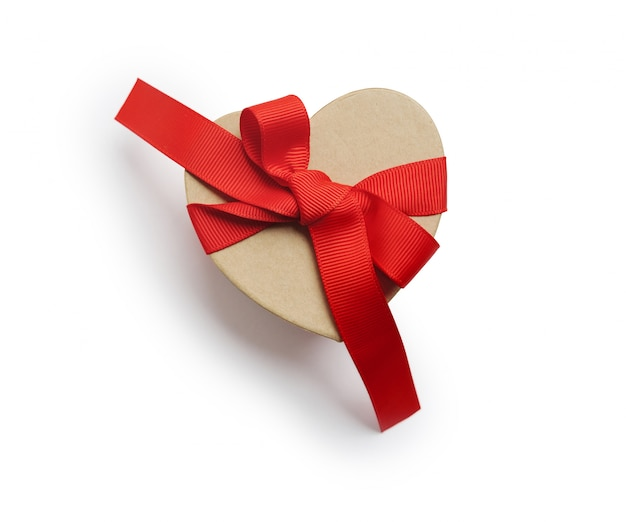 Wrapped vintage heart gift box with red ribbon bow, isolated clipping mask on white background, top view