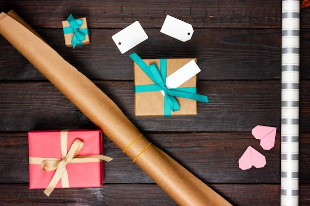 Wrapping paper, gifts and blank paper tags on a wooden table.
