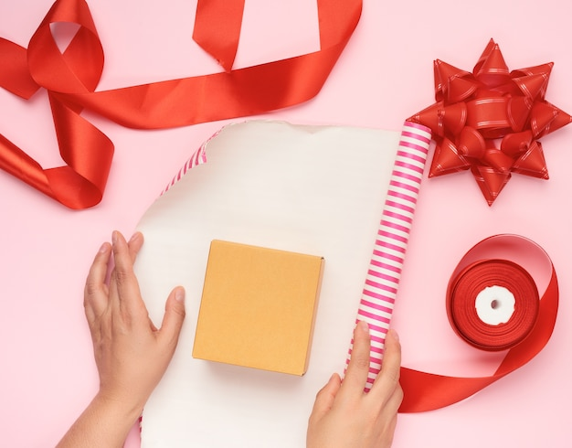 Wrapping paper roll, box and red silk ribbon with bow and items for gift wrapping