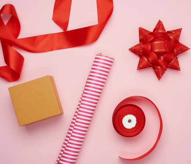 Wrapping paper roll, box and red silk ribbon with bow