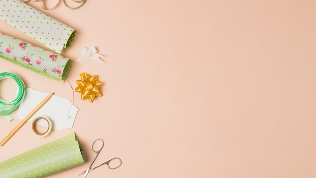Wrapping paper roll; sellotape; pencil; ribbon bows and scissor arranged in peach surface with space for text