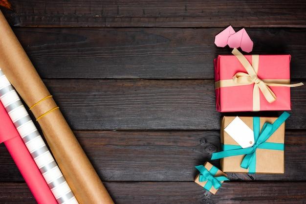 어두운 나무 테이블에 종이, 포장 된 선물 및 작은 마음을 포장. 위에서 봅니다.