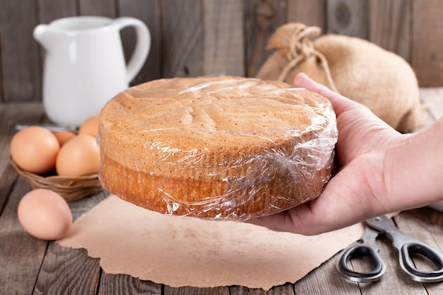 Wrapping sponge cake in plastic for storing on wooden background
