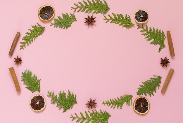 Wreath of fir twigs, star anise and cinnamon sticks and dry citrus on a pink background, christmas holiday background, flat lay