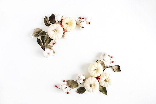 白い背景に白いカボチャ、赤い果実、ユーカリの枝で作った花輪フレーム。フラットレイ、トップビュー