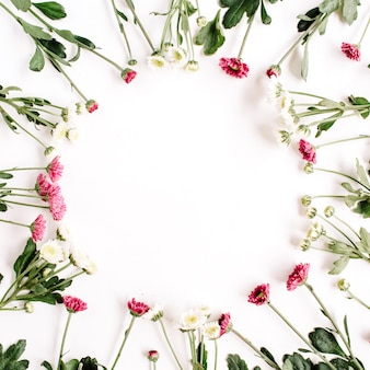 Wreath frame of red and white wildflowers, green leaves, branches on white surface
