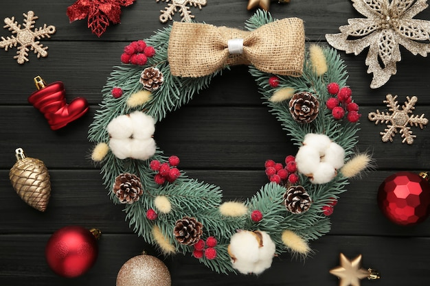 Wreath from fir, pine and spruce twigs, decorated with cotton, flowers ad christmas decoration on black wooden background. top view