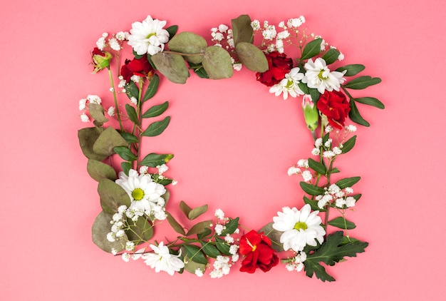 Wreath made from red and white flowers in front of peach background