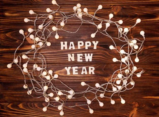 木製のテーブルのクリスマスライトで作られた花輪。明けましておめでとうございます2021