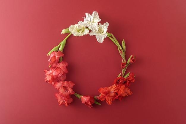 Венок из осенних цветов на темно-красном фоне. цветочная композиция.