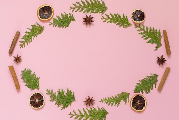 ピンクの背景にモミの小枝、スターアニスとシナモンの棒、乾燥した柑橘類の花輪、クリスマス休暇の背景、平置き