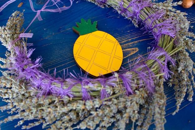青い木製のボードにラベンダーと黄色のパイナップルの花輪