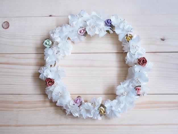 나무 배경에 작은 장미와 흰 꽃의 화환. 결혼식 장식을 위한 원형 꽃 프레임입니다.