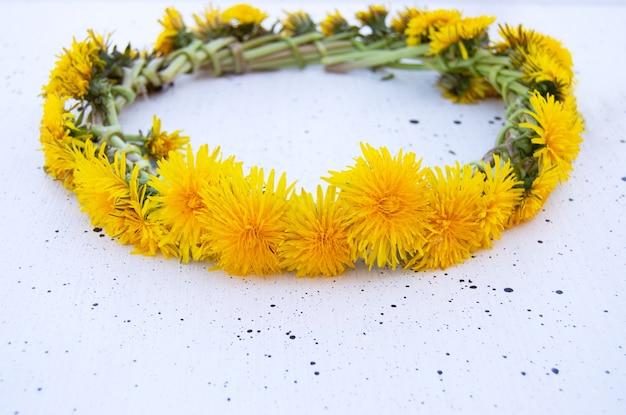 Венок из желтых одуванчиков на белом фоне