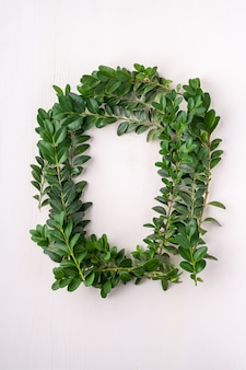 Buxus sempervirens緑の葉の花輪の正方形のフレームの葉白い木製の背景copyspaceテンプレートトップビューオーバーヘッド