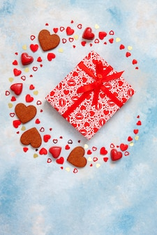 Wreath of sweets, cookies and heart figurines with gift box on  blue background.