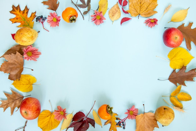 A wreath of various colorful autumn fruits and leaves over light blue background.