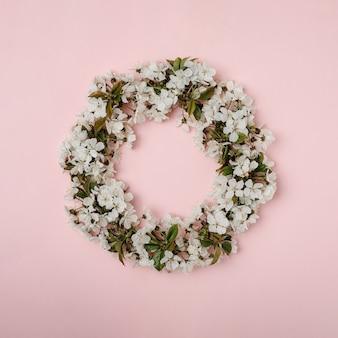 피는 벚꽃 잎과 분홍색 배경에 녹색 잎 화 환. 행복한 봄 휴가의 최소한의 창조적 인 개념.