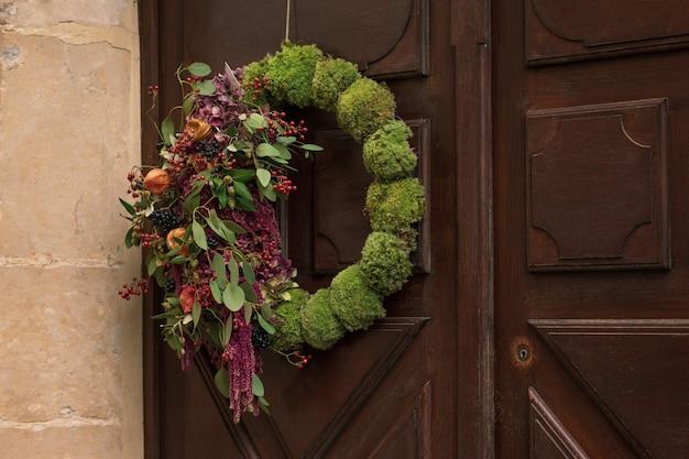 문에 매달린 붉은 열매와 마른 잎으로 화환.