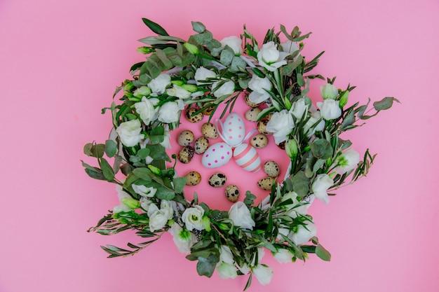 ピンクの背景に白いバラとイースターエッグと花輪。飾られた。上図
