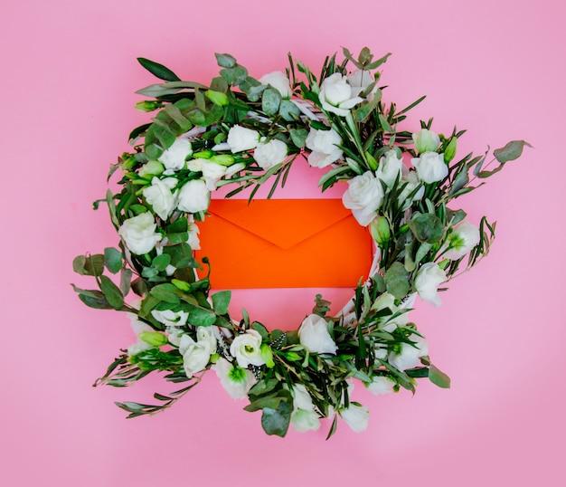 ピンクの背景に白いバラと封筒と花輪。飾られた。上図