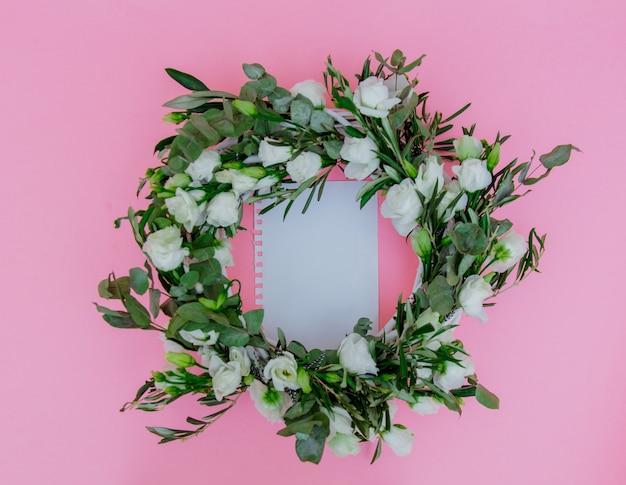 白いバラとピンクの背景にメモ用紙と花輪。飾られた。上図