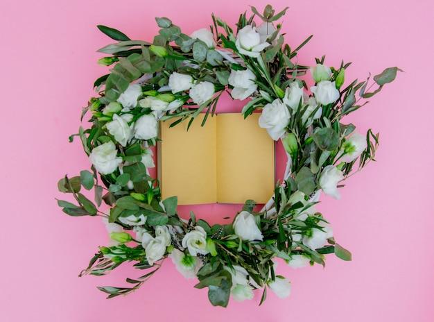 白いバラとピンクの背景に開いたレシピ本と花輪。飾られた。上図
