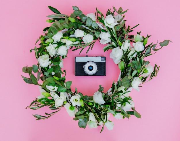 白いバラと白い背景の上のビンテージカメラと花輪。飾られた