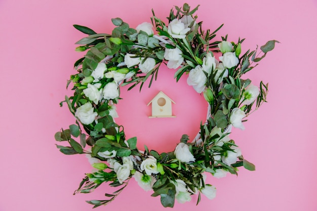 Wreath with white roses and nesting box on pink background. decorated. above view