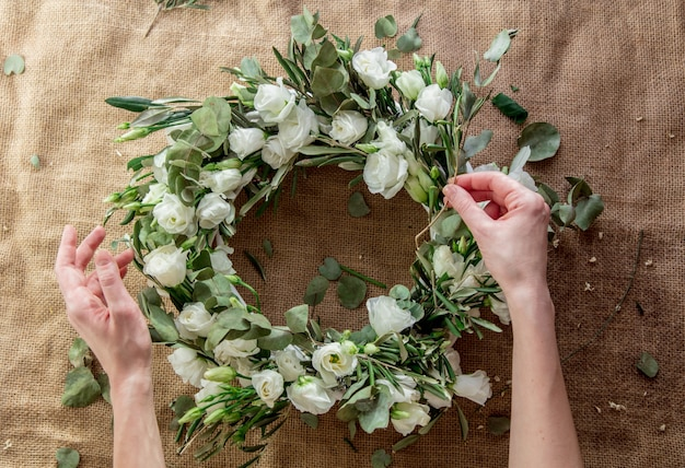 ジュートの背景に白いバラと花輪。飾られた